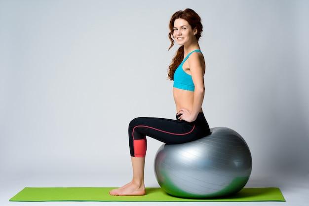 Młoda czerwona z włosami dziewczyna siedzi na gym piłce.