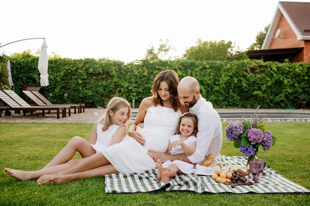 Młoda czteroosobowa rodzina z matką w ciąży, piknik na podwórku