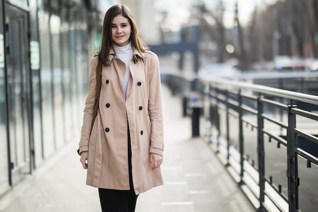 Młoda czuła brunetki dziewczyna chodzi po mieście w przypadkowych ubraniach