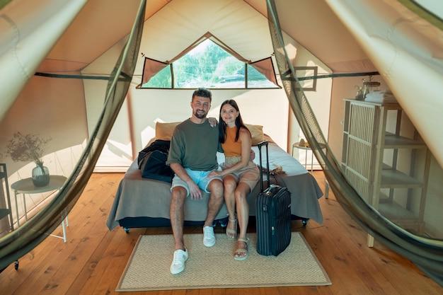 Młoda czuła para siedzi na podwójnym łóżku w domu glampingowym