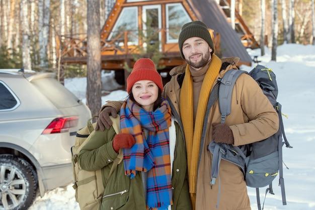 Młoda czuła para w ciepłej odzieży zimowej stojąca przed kamerą przed samochodem i wiejskim domem i patrząca na ciebie na zewnątrz