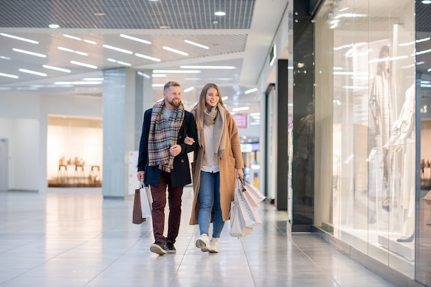 Młoda, czuła para w stylowej odzieży codziennej, niosąca papierowe torby, poruszając się po witrynach sklepowych w centrum handlowym