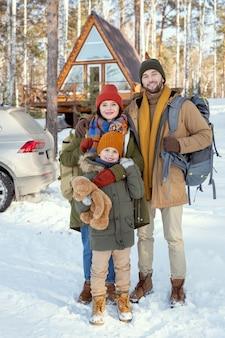 Młoda, czuła rodzina składająca się z trzech osób w ciepłej odzieży zimowej, stojąca przed kamerą przed swoim wiejskim domem i patrząca na ciebie na zewnątrz