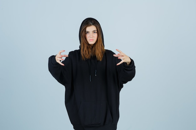 Młoda dama agresywnie trzymająca ręce w obszernej bluzie z kapturem, spodniach i wyglądająca na zirytowaną. przedni widok.