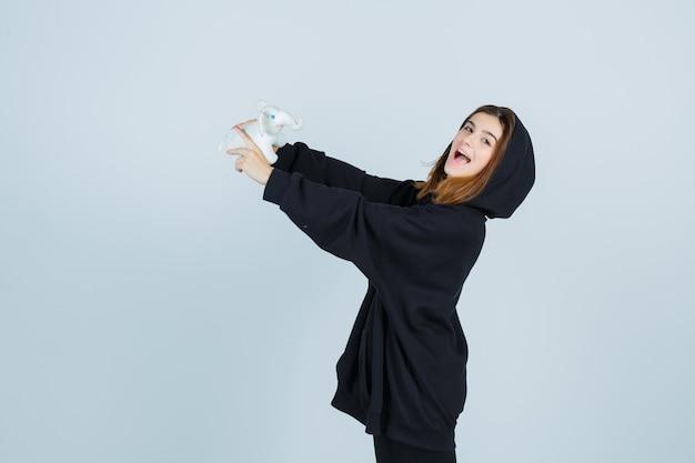 Młoda dama bawi się zabawką słonia w obszernej bluzie z kapturem, spodniach i wygląda na szczęśliwą, widok z przodu.