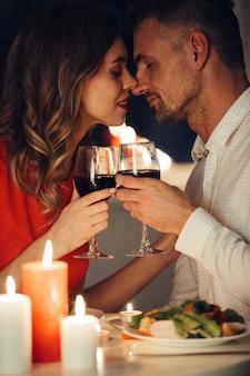 Młoda dama całuje swojego wspaniałego mężczyznę podczas romantycznej kolacji