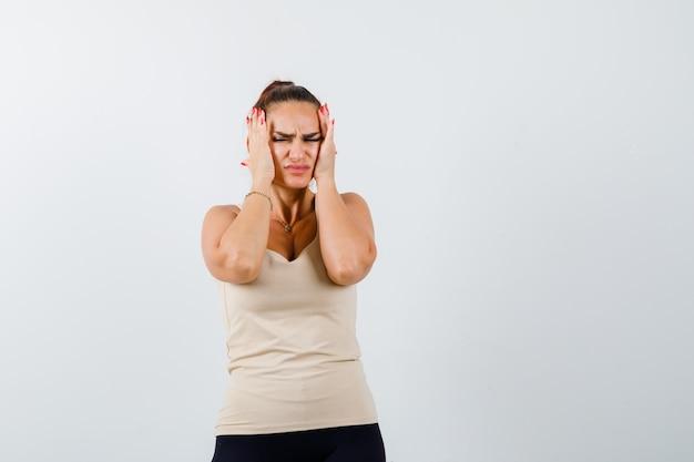 Młoda dama cierpi na silny ból głowy w podkoszulku i wygląda na zirytowaną. przedni widok.