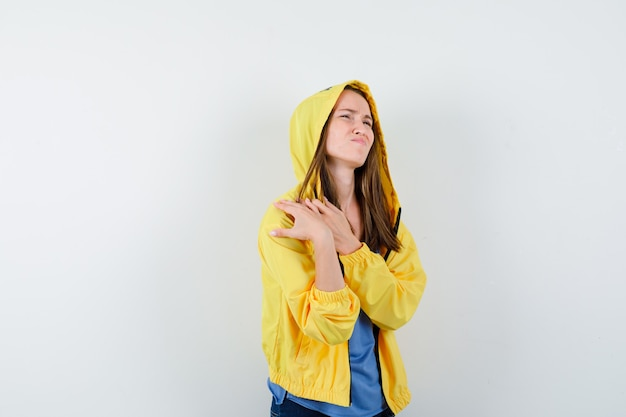 Młoda dama cierpiąca na ból barku w koszulce, kurtce i wyglądająca na zmęczoną, widok z przodu.
