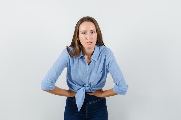 Młoda dama cierpiąca na ból brzucha w niebieskiej koszuli, spodniach i wyglądająca marnie.