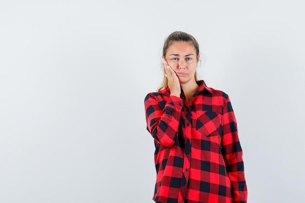 Młoda dama cierpiąca na ból zęba w koszuli w kratę i niewygodna