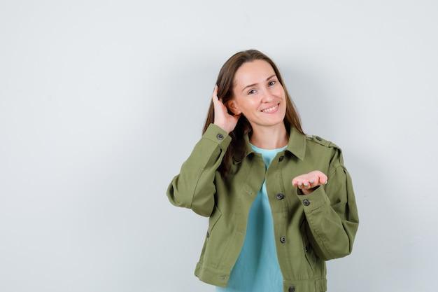 Młoda dama czesze włosy ręką, pokazując coś w koszulce, kurtce i patrząc na radosne, widok z przodu.