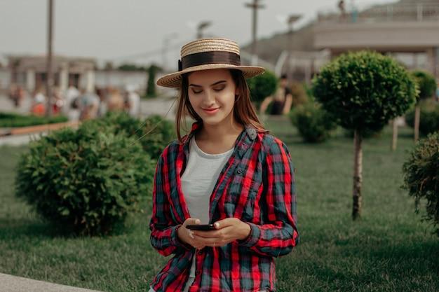 Młoda dama czyta wiadomość w telefonie chodzi w parku.