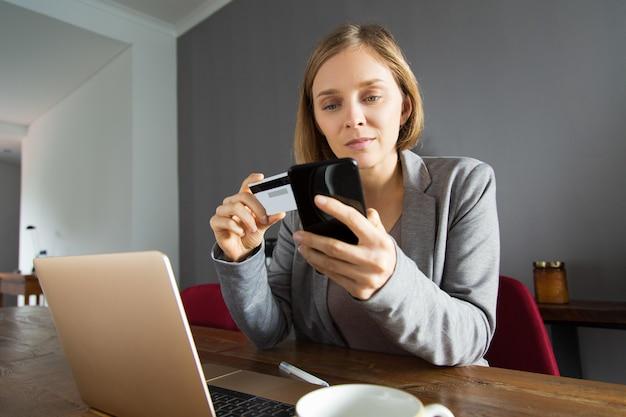 Młoda dama dokonywania płatności online za pomocą smartfona