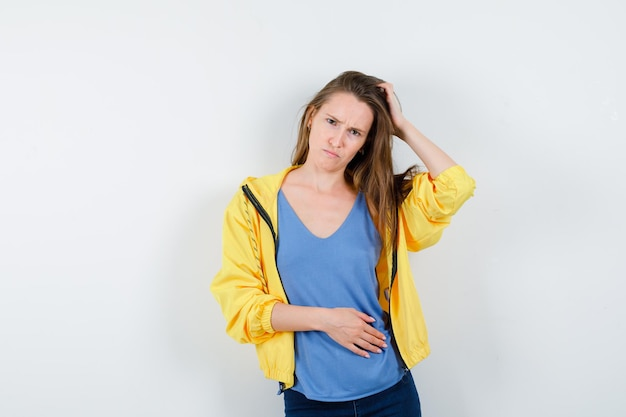 Młoda dama drapie się po głowie, krzywiąc się w koszulce, kurtce i patrząc z wahaniem