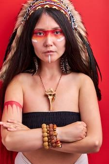 Młoda dama etniczne z płoci na głowie na białym tle nad czerwoną ścianą