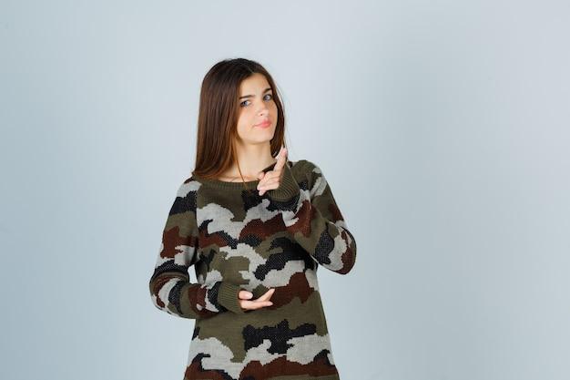 Młoda dama grozi palcem w swetrze i wygląda pewnie