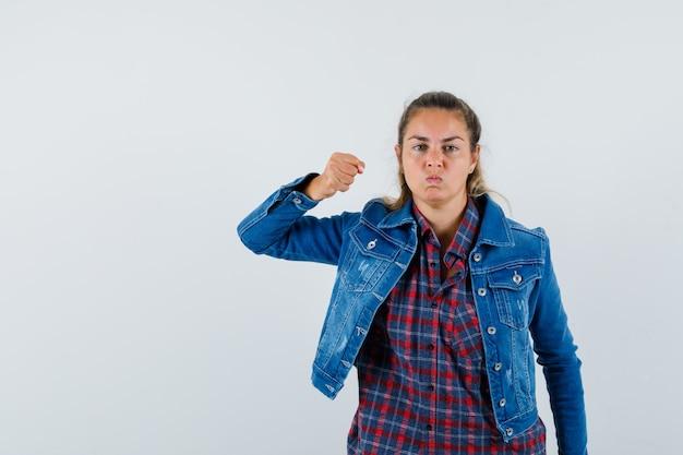 Młoda dama grozi pięścią w koszuli, kurtce i wygląda złośliwie, widok z przodu.