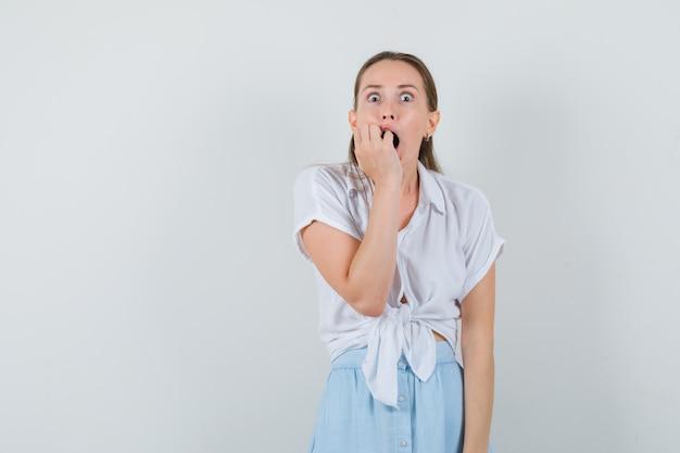 Młoda dama gryząca emocjonalnie pięść w bluzkę, spódnicę i wyglądająca na przestraszoną