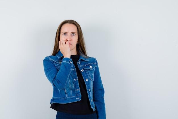 Młoda dama gryzie paznokcie w bluzkę, kurtkę i wygląda na niespokojną. przedni widok.