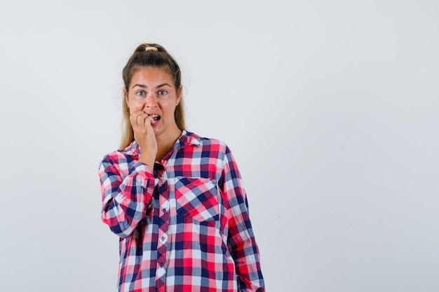 Młoda dama gryzie paznokcie w koszuli w kratę i wygląda na podekscytowaną. przedni widok.