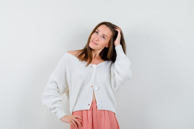 Młoda dama grzebień włosy ręką w swetrze i spódnicy wyglądającej atrakcyjnie na białym tle
