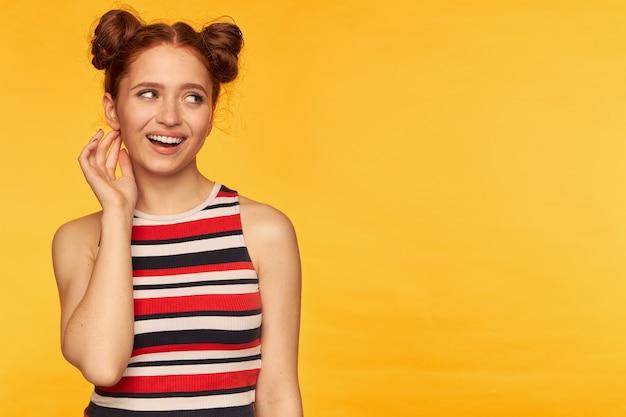 Młoda dama, ładna ruda kobieta z dwiema bułeczkami. ubrana w pasiasty podkoszulek i wyglądająca zalotnie, dotykając jej ucha. koncepcja emocjonalna. patrząc w prawo na miejsce kopiowania nad żółtą ścianą