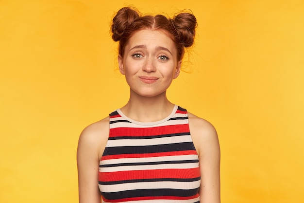 Młoda dama, ładna ruda kobieta z dwiema bułeczkami. ubrany w pasiasty podkoszulek i wyglądający na coś oczekującego, odizolowany na żółtej ścianie