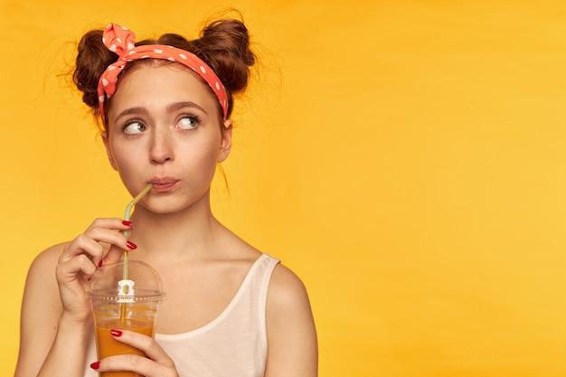 Młoda dama, ładna ruda kobieta z dwoma bułeczkami i opaską w kropki. nosi białą koszulę i zastanawia się, robiąc łyk soczystego świeżości. oglądanie w prawo w miejsce kopiowania nad żółtą ścianą