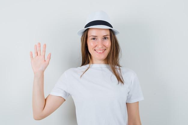 Młoda dama macha ręką, by się pożegnać w białym t-shircie i wygląda wesoło