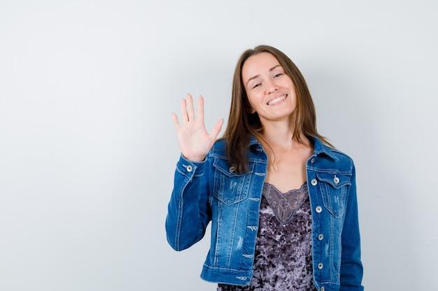 Młoda dama macha ręką na powitanie w bluzce, dżinsowej kurtce i wygląda wesoło, widok z przodu.