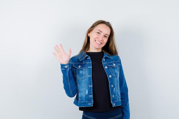Młoda dama macha ręką na powitanie w bluzce i wygląda na zadowoloną. przedni widok.