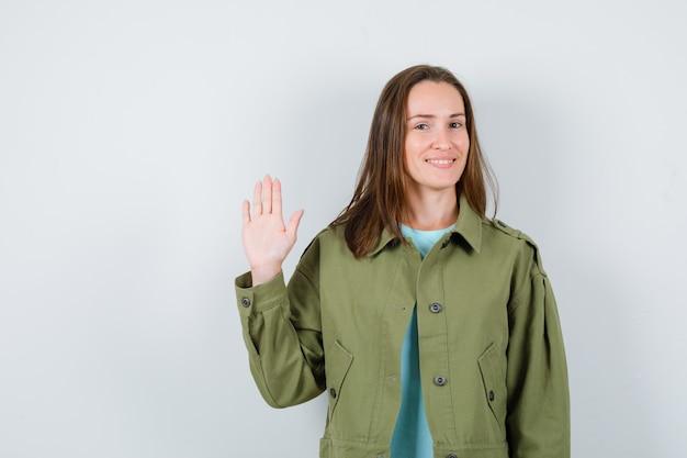 Młoda dama macha ręką na powitanie w koszulce, kurtce i ładny wygląd. przedni widok.