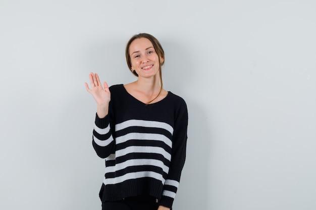 Młoda dama macha ręką na powitanie w koszuli i wygląda zadowolona