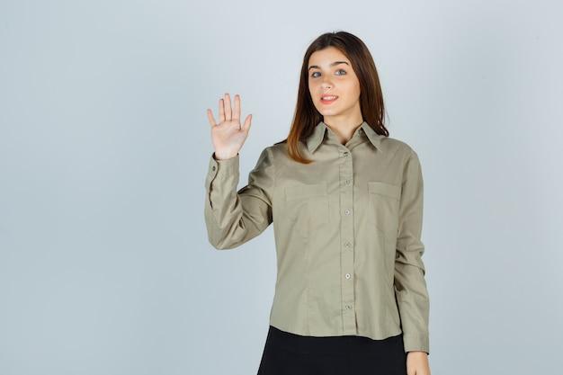 Młoda dama macha ręką na powitanie w koszuli, spódnicy i patrząc wesoło, widok z przodu.