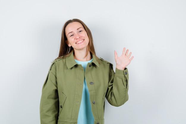 Młoda dama machając ręką na powitanie w koszulce, kurtce i patrząc wesoło, widok z przodu.