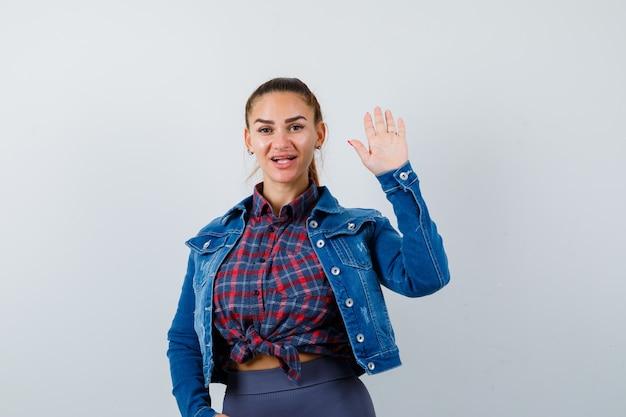 Młoda dama machająca ręką na powitanie w koszuli, kurtce i patrząc zdziwiona. przedni widok.