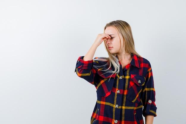 Młoda dama masuje mostek nosa w kraciastej koszuli i wygląda na wyczerpaną. przedni widok.