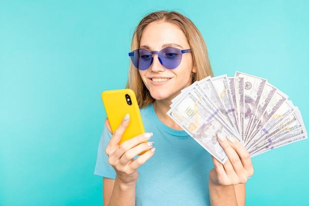 Młoda dama na białym tle na niebieskim tle. patrząc na aparat pokazujący wyświetlanie telefonu komórkowego z pieniędzmi.