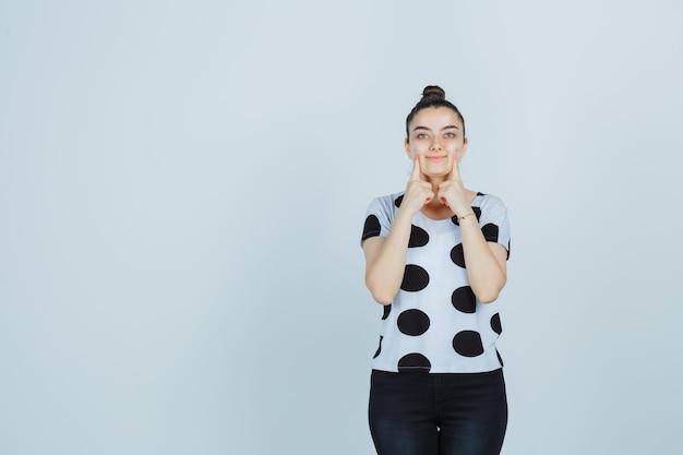 Młoda dama naciskając palce na policzkach w t-shirt, dżinsy i ładny widok z przodu.