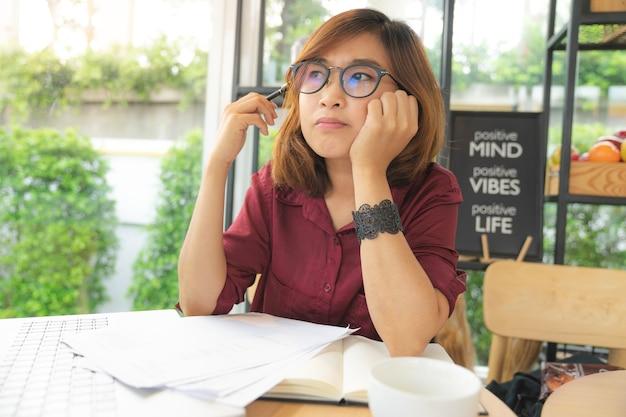 Młoda dama nosi okulary pracujące na laptopie i myśli o pomyśle w kawiarni