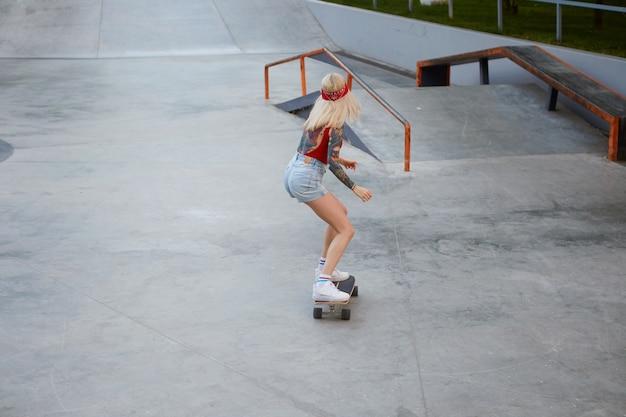 Młoda dama o blond włosach, z wytatuowanymi ramionami, ubrana w czerwoną koszulkę i dżinsowe szorty, z dzianinową bandaną na głowie, lubi jeździć na longboardzie w skateparku.