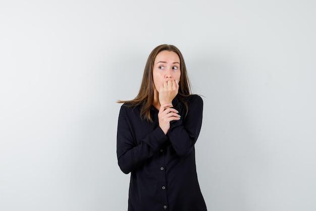 Młoda dama obgryza paznokcie i wygląda na zaniepokojoną