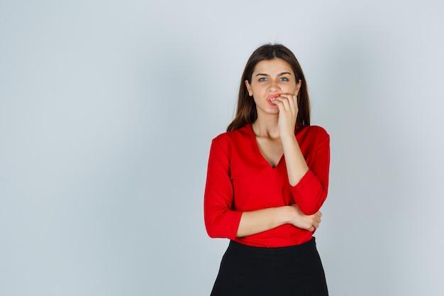 Młoda dama obgryza paznokcie w czerwonej bluzce, spódnicy i wygląda na zestresowaną
