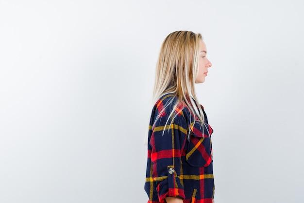 Młoda dama odwracająca wzrok w koszuli w kratę i wyglądająca na pewną siebie. przedni widok.