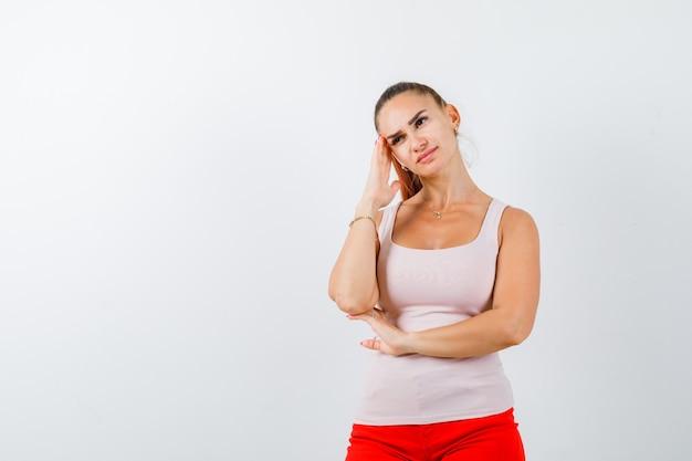 Młoda dama, opierając głowę na dłoni w beżowym podkoszulku i wyglądającej zamyślonej