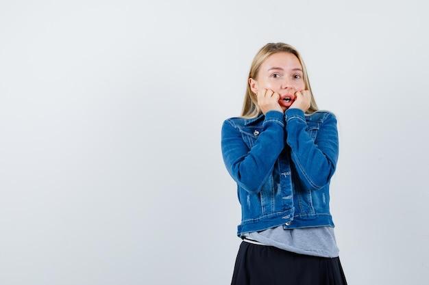 Młoda dama opierając podbródek na rękach w t-shirt, kurtka dżinsowa, spódnica i ładny wygląd.