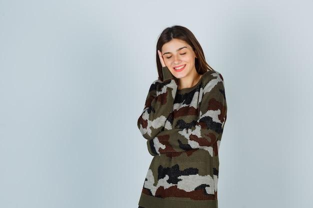 Młoda dama opierając policzek na dłoni w swetrze, spódnicy i wyglądającej wesoło