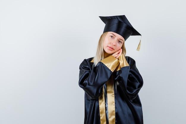 Młoda dama opierając policzek na rękach w akademickim stroju i patrząc sennie.