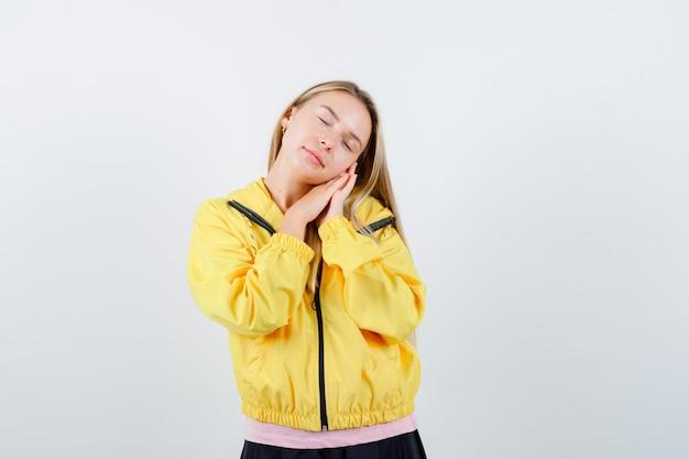 Młoda dama opierając policzek na rękach w t-shirt, kurtce i patrząc śpiący