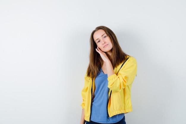 Młoda dama opierając policzek pod ręką w koszulce, kurtce i ładny wygląd. przedni widok.